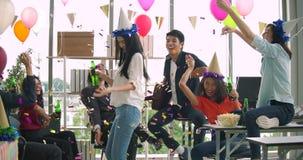 Equipo de baile y de divertirse de celebrar con la tostada y de tintinear de la gente joven aumentando los vidrios en su oficina almacen de video