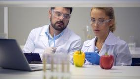 Equipo de científico que inyecta las sustancias químicas en las pimientas en laboratorio almacen de video