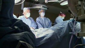 Equipo de cirujanos que realizan la cirugía (4 de 15) almacen de video