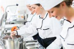 Equipo de cocineros en el proceso de producción del abastecimiento del sistema imagen de archivo