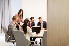 Equipo de colegas jovenes que trabajan junto en una oficina Imagen de archivo libre de regalías