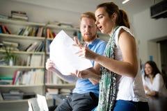Equipo de colegas que se inspiran junto mientras que trabaja en oficina moderna imagen de archivo