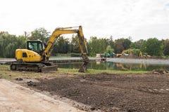 Equipo de construcción pesado Excavador amarillo en el emplazamiento de la obra Fotografía de archivo libre de regalías