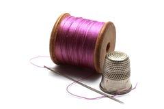 Equipo de costura - carrete del hilo del algodón con un dedal y una aguja Fotos de archivo