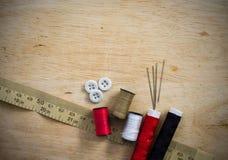 Equipo de costura con el hilo y agujas en el fondo de madera Imagenes de archivo