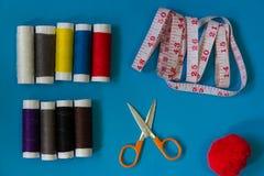 Equipo de costura plano de la endecha, tijeras, carrete multicolor del hilo, cinta métrica en fondo azul Imagen de archivo