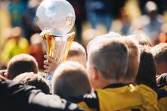 Equipo de deporte de los niños con el trofeo Niños que celebran campeonato del fútbol fotos de archivo