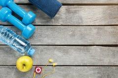 Equipo de deportes en un fondo gris, de madera, pesas de gimnasia, agua en una botella, jugador de la manzana foto de archivo libre de regalías