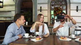 Equipo de desarrolladores que trabajan con los vidrios de la realidad virtual durante una reunión de negocios Colegas jovenes del almacen de video