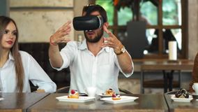 Equipo de desarrolladores que trabajan con los vidrios de la realidad virtual durante una reunión de negocios Colegas jovenes del metrajes