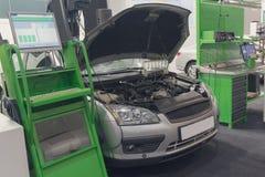 Equipo de diagnóstico y un coche en un servicio del coche imagen de archivo