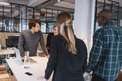 Equipo de diseñadores jovenes que trabajan junto en oficina Imagen de archivo libre de regalías