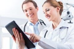 Equipo de doctores en clínica con la tableta Imagen de archivo
