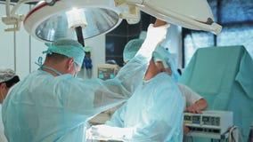 Equipo de doctores en ropa y máscara estéril durante cirugía C?mara lenta almacen de video