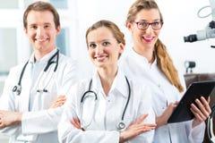 Equipo de doctores jovenes en clínica con el ordenador de la tableta Imagenes de archivo