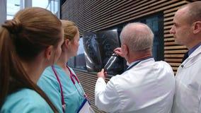 Equipo de doctores que discuten sobre informe de la radiografía metrajes