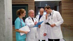 Equipo de doctores que discuten sobre informe médico almacen de video