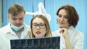 Equipo de doctores que miran imágenes de MRI media Doctores en MRI de observación uniforme blanco y opiniones de la parte sobre d almacen de metraje de vídeo