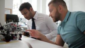 Equipo de dos aserradores superiores que discuten los robots móviles