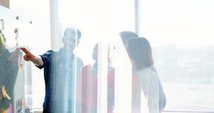 Equipo de ejecutivos de operaciones que discuten sobre el tablero de cristal