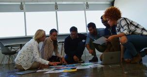 Equipo de ejecutivos que discuten sobre el documento en la reunión almacen de metraje de vídeo