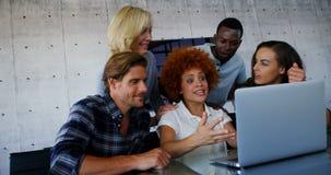 Equipo de ejecutivos que discuten sobre el ordenador portátil metrajes