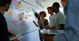 Equipo de ejecutivos que discuten sobre notas pegajosas sobre whiteboard almacen de metraje de vídeo