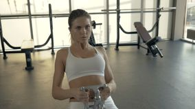 Equipo de elevación de la aptitud del culturista de la mujer para el músculo de entrenamiento detrás en club del gimnasio almacen de metraje de vídeo
