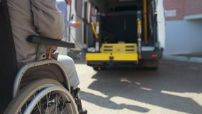 Equipo de elevación para las personas con discapacidades - el hombre en silla de ruedas levanta para arriba en el coche almacen de video