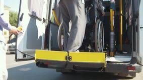 Equipo de elevación para las personas con discapacidades en el minivan - el hombre en la silla de ruedas sube abajo del minivan almacen de video