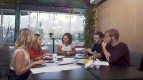 Equipo de empresarios acertados jovenes que se encuentran en la tabla de la sala de reunión que discute informe financiero Tabla  almacen de video