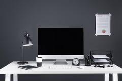 Equipo de escritorio con la pantalla en blanco, la carta de negocio, el reloj y los materiales de oficina imagen de archivo libre de regalías