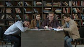 Equipo de estudiantes que estudian junto para el examen almacen de metraje de vídeo