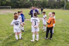 Equipo de fútbol de los niños con el entrenador Fotos de archivo