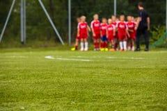 Equipo de fútbol de la juventud con el entrenador en echada; Fondo borroso del fútbol Imagen de archivo