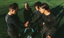 Equipo de fútbol que apila las manos en el campo de fútbol Imagen de archivo libre de regalías