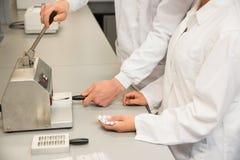 Equipo de farmacéuticos que usan la prensa para hacer píldoras Fotos de archivo libres de regalías