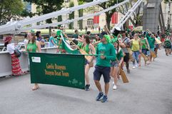 Equipo de Gaelic Dragon del día del ` s de St Patrick que cruza el puente de Cavengah en Singapur Fotografía de archivo libre de regalías