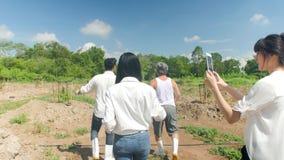 Equipo de granjero Walking en un campo y el hablar en la inspección de la calidad
