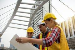Equipo de hembras jovenes y de ingenieros de sexo masculino que trabajan en la construcción favorable imagenes de archivo