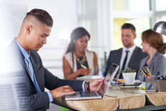 Equipo de hombres de negocios acertados que tienen una reunión en la oficina iluminada por el sol ejecutiva Foto de archivo