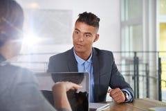 Equipo de hombres de negocios acertados que tienen una reunión en la oficina iluminada por el sol ejecutiva Imagen de archivo libre de regalías