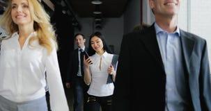 Equipo de hombres de negocios que caminan en oficina mientras que llamada de teléfono asiática de la respuesta de la empresaria metrajes