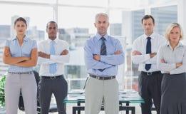 Equipo de hombres de negocios que se colocan con los brazos doblados Fotos de archivo libres de regalías