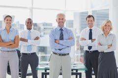 Equipo de hombres de negocios sonrientes que se colocan con los brazos doblados Foto de archivo