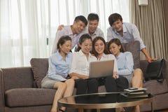 Equipo de hombres de negocios sonrientes que trabajan junto y que miran un ordenador portátil Imagen de archivo