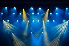 Equipo de iluminación en la etapa del teatro durante el funcionamiento Los rayos ligeros del proyector a través del humo imagen de archivo
