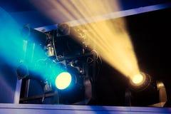Equipo de iluminación en la etapa del teatro durante el funcionamiento Los rayos ligeros del proyector a través del humo imagen de archivo libre de regalías