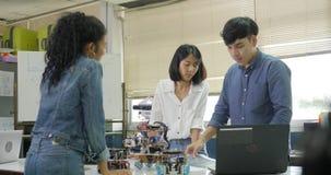 Equipo de ingeniero electrónico que trabaja junto, colaborando en un proyecto para construir el robot almacen de video