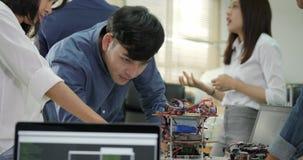 Equipo de ingeniero electrónico que trabaja junto, colaborando en un proyecto para construir el robot almacen de metraje de vídeo